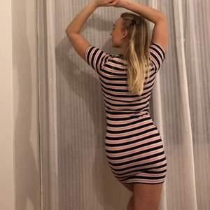 Snygg svart/ vit/ rosa tight klänning i stretchigt tyg. Man får väldigt fin figur i den!! Använd en hel del men fortfarande i bra skick.