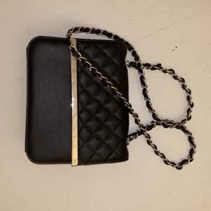 En svart fin väska med silver detaljer, köpt på glitter från nått år sedan.