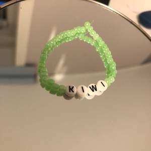 Ett armband med texten 'kiwi' inspirerat av en Harry Styles låt. Man kan även göra egna designs🌍 1 för 25, två för 40, tre för 50:)