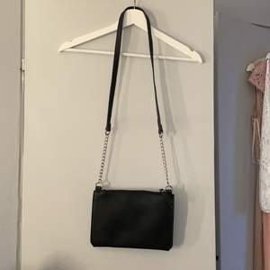 """En jättefin liten väska i fake skinn/läder! Den är köpt på Glitter och den är aldrig använd då jag har för många! Perfekt storlek om man gillar lite mindre väskor. Den är """"platt"""" men ändå väldigt rymlig🤍"""