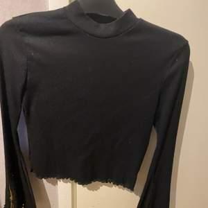 Långärmad svart tröja med ärmar som har en guldkedja som detalj som man kan dra upp och ner på.