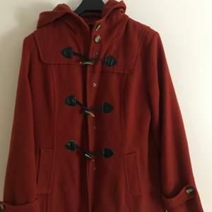 En fin kappa som har väldigt fina knappar med en fin färg och har andra knappar till som går att sätta ihop. Kappan har aldrig blivit använd. Skulle passa perfket med en tjock tröja under och sedan den över:)