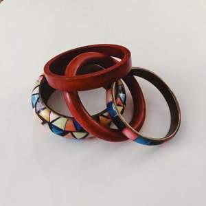 En samling färgglada armband i trä, metall och sten som är i toppskick!