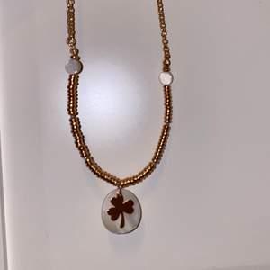 Ett rosé färgat halsband med vita pärlor och en treklövers symbol i mitten, jätte fin köpte den i sommras aldrig använt den har inte hunnit använda den.
