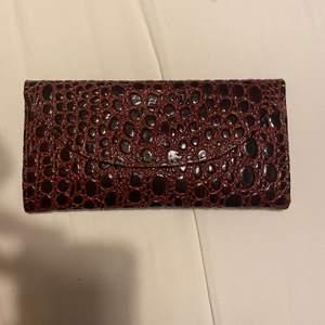 Säljer denna vinröda plånbok. Den är oanvänd. Den har skit coola detaljer både utifrån och inuti. Undrar man över något så är det bara att kontakta mig.