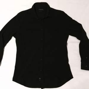 Kolsvart skjorta i lite grövre tyg som sitter som ett smäck!  SLIMFIT Edsast använd 1 gång.