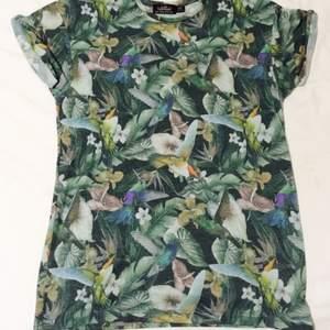 Mjuk go t-shirt med fåglar och blommor i tyget.