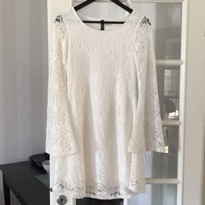 Säljer en helt oanvänd vit spets klänning med långärmade  utsvängda armar. Har bara spets på armarna med överallt annars är det tyg under så den är ej genomskinlig. Säljer för 100 kr. Storlek 36. Köparen står för frakten!