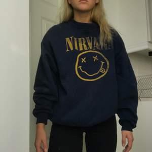 En vintage Nirvana sweatshirt i en mörkblå färg. Köpt i Köpenhamn. Jag som är S bär den lite oversized. Jag skulle säga att den passar XS-M.