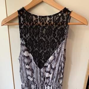 Gråvit klänning i ormskinnsmönster 🐍 Kort fram och längre bak med svart spets på ryggen. Samfraktar gärna med nåt annat litet! (Skärpet ingår inte)