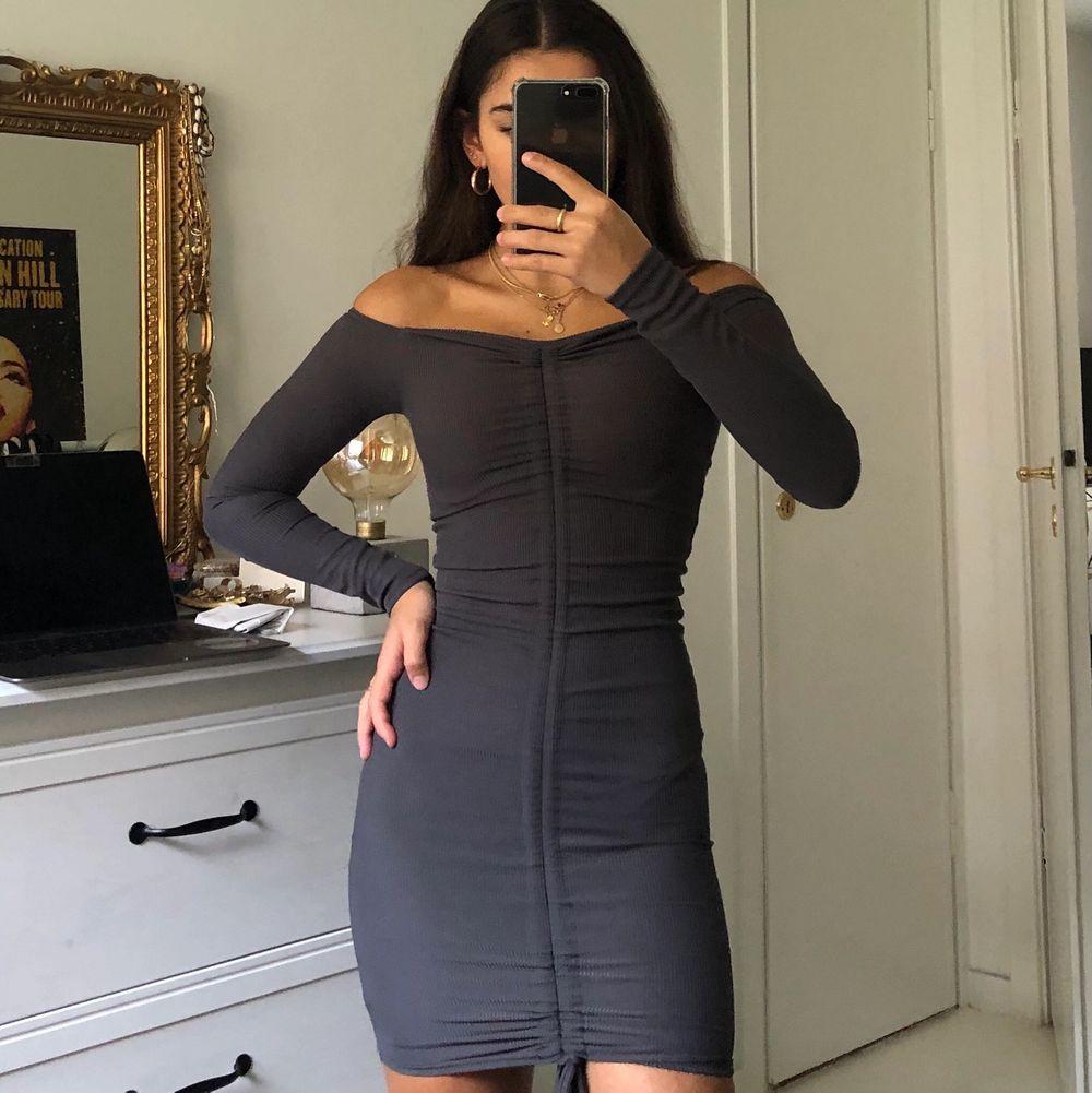 snygg klänning i färgen charcole. Den går att justera längden med snöret/detaljen i mitten. säljer då den är lite för liten för mig. Aldrig använd, lappen finns kvar. Klänningar.