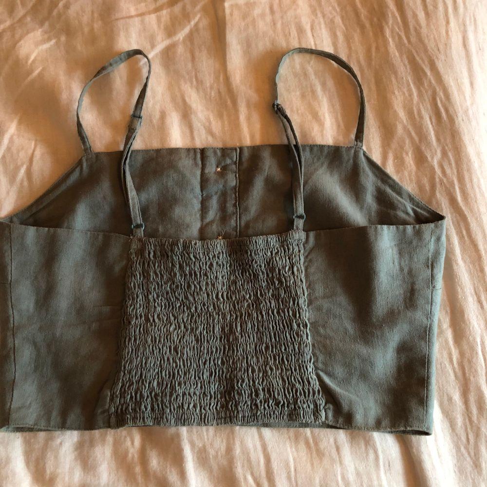 Ett kort turkost linne i linnetyg med knappar och resår i ryggen, tyvärr för litet för mig men superfint till sommaren. Toppar.
