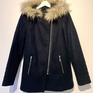 Ny kappa i mörkblå, nästan svart med päls som ser äkta ut. Två fickor fram med dragkedjor i silver. Från New Look i storlek 10, motsvarar storlek 36. Materialet är i ull och polyester. Säljes då den tyvärr är för liten för mig. Jackan är aldrig använd.