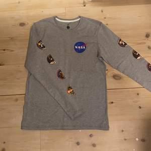 """Grå långärmad cool NASA t-shirt med runda tryck på ärmarna och litet NASA tryck fram.♥️ Material (mjukt och bekvämt) 60% cotton/bomull och 40% polyester. Nyskick/mycket bra skick då den endast är testad. Passar bra med mycket, men tex jeans, shorts eller bara som en sovtröja. Storlek M, men ganska liten i storleken.  DM vid intresse/frågor/fler bilder.❣️ (Det kan du göra här under där det står """"kontakta"""") Avhämtning på Södermalm eller frakt till självkostnadspris.:)"""