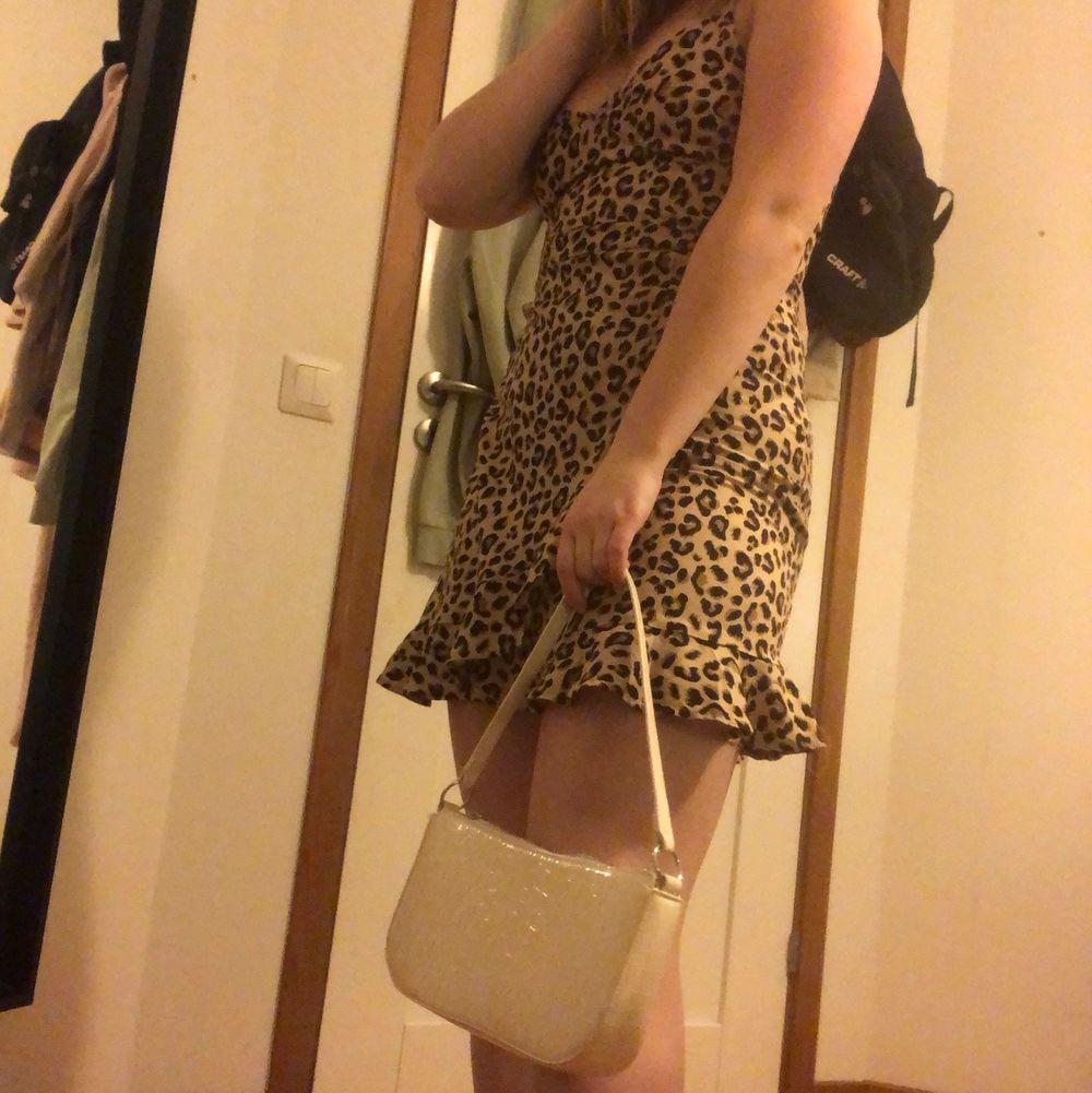 Kort klänning i leopardmönster som sitter ganska tajt från H&M i strl 36. Klänningar.