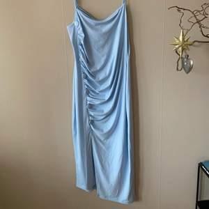 Klänningen är ljusblå med sju detaljknappar och en slits, den är i storlek EU 46 och oanvänd. Frakt 4