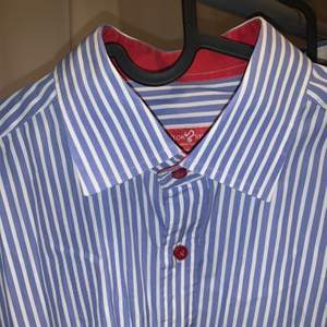 Skräddarsydd randig skjorta med röda knappar, i bra skick. Sitter som en stl L slim fit (man men passar kvinnor med). Sitter som en oversized skjorta om du har typ stl S-M.