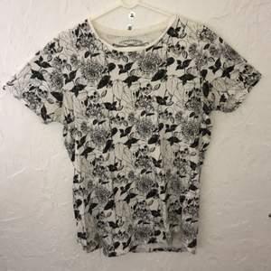 Vit t-shirt med dödskalletryck och blommor. Från Jack & Jones. Svart/vit. Storlek M. 100% bomull. Ett par cm längre bak än fram.
