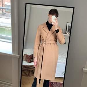 Kamelfärgad kappa i ull från ICHI, storlek 38. Väl använd men i gott skick! Fler bilder kan ordnas vid intresse. Säljes då den inte längre kommer till användning. Nypris ca 1200kr.
