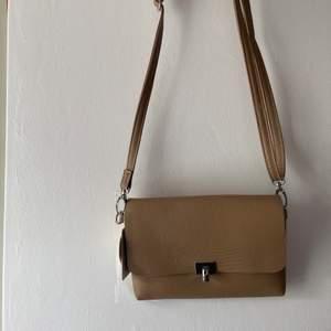 Snygg beige väska, aldrig använd, prislappen är kvar. Från Primark. Axelbandet är justerbart.