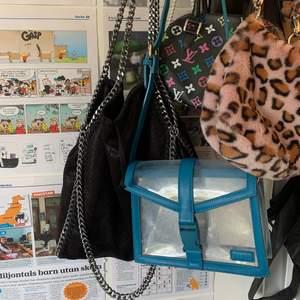 """Säljer denna fina väska som förut var min favvoväska! Den är från na-kd och har några få repor på den genomskinliga """"utsidan"""", (se bild 3). Annars i bra skick! Väskan går att göra både längre och kortare än vad den är på bilden! Frakten ingår i priset! Skriv på dm om du är intresserad!💙💙"""