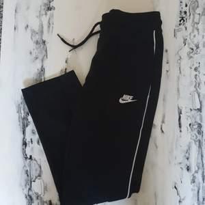 Ett par svarta Nike byxor i lite sportig stil men som även passar till vardags eller hemma. Nike logga på ena benet samt en vit rand längs bägge ben. Byxorna har snören i midjan. Kontakta mig för bild hur de sitter på. De är knappt använda så i bra skick.