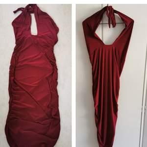 Mörkröd tie up halterneck klänning från Club L. Klänningen går ner under knäna och har öppen rygg. Adrig använd storlek uk 16 ~ 42-44. 50kr.