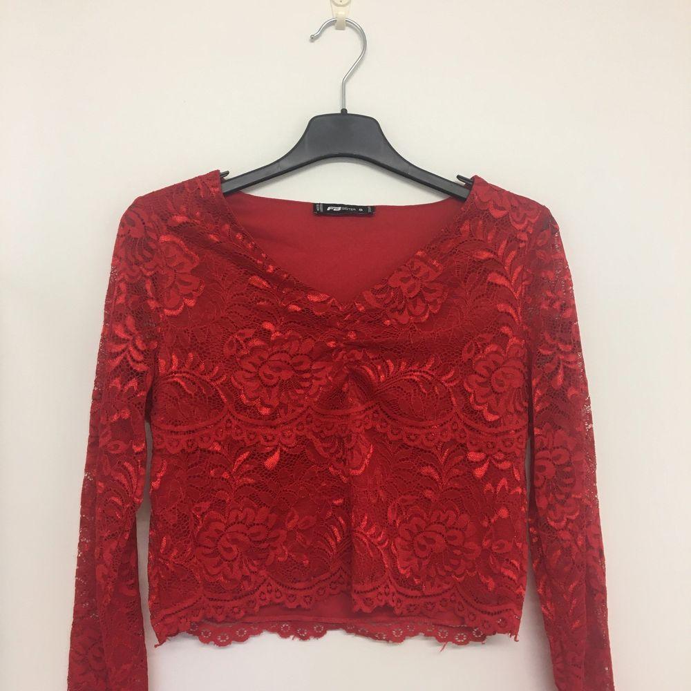 Röd långärmad tröja i spets. Använd ca 2 ggr. Används ej längre.. Blusar.