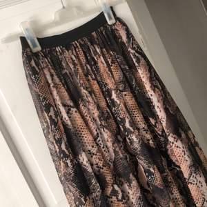 Mönstrad kjol i transparant yttertyg och svart innerkjol i bomull. Snygg och modern till en vanlig enfärgad topp. Resår i midjan så funkar både som strl S och M. Använd fåtal gånger.