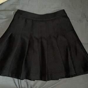Svart skit snygg veckad kjol som säljs då jag har en liknande. Som man ser på andra bilden så funkar dragkedjan men sitter lite löst och trasig nedtill, därav de lite lägre priset. Men det är lätt att laga! Annars super bra kvalite och jätte söt!