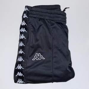 Svarta mjukisbyxor från kappa, raka i benen med logo längs hela sidan. Resår i midjan som man oxå kan knyta. Storlek XS (unisex) köpta från Junkyard. Sparsamt använda.