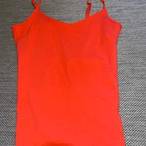 Rött bas linne i mjuk trikåkvalitet med smala reglerbara axelband. Linnet är fodrat över bysten.