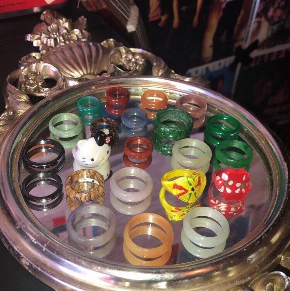 """Säljer fler av mina super snygga kristall ringar!!🥰alla ringar är utav en sorts kristall/ädelsten förutom det gula hjärtat, den röda blomman (plast), de två hematit ringarna till vänster (finns även i fler storlekar, sägs även att hematit går itu ifall den absorberar för mycket negativ energi) och till sist min Hallo Kitty ring som är den ända reglerbara!!💞 jag kommer att sälja plast ringarna och Hallo Kitty ringen för 50kr, hematit ringarna för 60kr och sedan alla kristall ringar för 80kr då de är i fin kvalitet och inköpta dyrt. Den tjockaste kristallringen (den gröna) kommer jag sälja för 110kr pga dess storlek!!🥰🥰 om du är intresserad av att köpa, vill ha fler bilder eller bara har en fråga så är det bara att trycka på """"kontakta"""".💓 (frakten ingår inte i priset, om du köper flera blir det självklart paketpris!!)☺️. Accessoarer."""