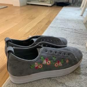 Helt oanvända gråa tygskor med blommor på! Skosnöret ligger separat!