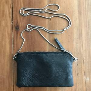 Bought this at STHLM Stadsmission. Mini pouch with zipper closing and a chain strap. Lining has a couple of stains, but you can't tell when it's zipped! The pull tab is a bit distressed. Price clearly reflects the state of the item. Disclaimer: Please expect some general wear in all secondhand pre-owned items as they have lived a previous life, so do not expect a mint item.