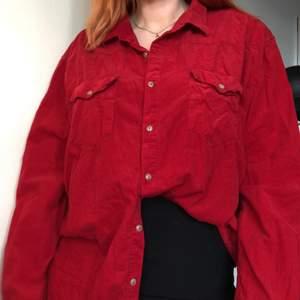 Röd skjorta i velourliknande material. Kan användas på flera sätt, exempelvis instoppad, knuten i midjan eller över axlarna med en snygg topp under😍