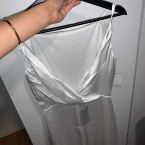 Så fin och trendig vit klänning i satin, öppen rygg och rak skurning, säljer då den tyvärr aldrig kommit till användning, så helt i nyskick!💗 perfekt till student eller liknande💞  nypris 700kr