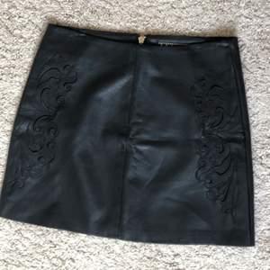 En svart skinnkjol från Kardashian Kollection. Mycket gott skick med har broderi på framsida och en guldig dragkedja baktill. Den är i storlek 6 (s) men för mig som brukar ha typ S-M är den lite liten för. Skriv för bilder elr info😙