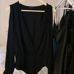 Bodysuit nelly i storlek L med öppning vid ärmarna