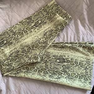 Ett par helt nya utsvängda byxor med ormmönster från weekday, storlek 38  i verkligheten är färgen starkare, lite mer neongröngul