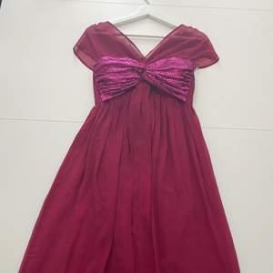 En rosa väldigt lång klänning som använts en gång.