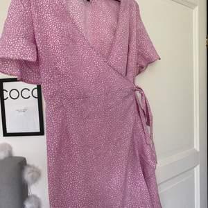 Rosa tunn klänning med vita prickar perfekt till sommaren! Tvättad 1 gång. Omlott klänning - du knyter den när du tar på dig den.