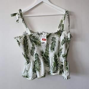 Ett fint vitt linne med gröna detaljer på. Längden på banden går att ändra.           Aldrig använd