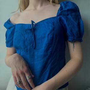 Blå blus med knytning framtill från H&M. Blusen går att använda både som offshoulder och vanlig. Baktill är blusen veckad.