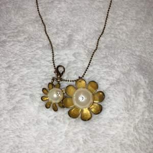 Säljer detta fina halsband med 2 gulliga blommor som hänge. Kedjan är väldigt lång. Man kan även hänga ditt ett till hänge, som man ser på första bilden🤍🤍