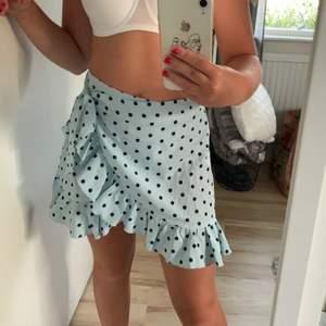 Säljer denna fina prickiga kjolen från Shein. Den är ljusblå/mintblå med svarta prickar😊 Man knäpper den med en knapp och sedan knyter i sidan🥰