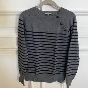 Grå och svart randig tröja från Zadig Voltaire med knappar. Har några slitningar vid händerna och ett litet hål vid halsen (se sista bilden). Storlek 16 år, vilket motsvarar en S/XS . 95% ull och 5% kashmir.