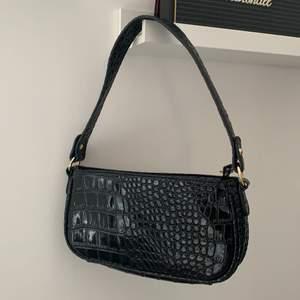 Baugettebag/ baugette-väska i ett svart orm/krokodil material. Väskan är aldrig använd då jag råkade köpa 2 likadana. Det får plats med ganska mycket, väskan har inga innerfickor. Hör av er för mer frågor eller fler bilder!😁