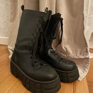 Svarta boots med hög platå, snörning samt dragkedja. Skon går upp mot vaden. 🤍