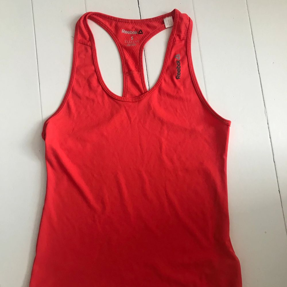 Orangerött träningslinne från Reebok. Sparsamt använt. Frakt tillkommer på 45kr❤️. Huvtröjor & Träningströjor.